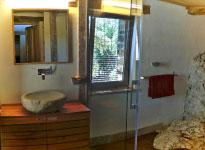Salle de bain exceptionnelle avec grande douche, roche apparente et caillebotis en bois exotique.