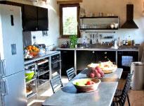 Luminaires haut de gamme, poutres, sol en marbre et  mobilier design pour la cuisine toute équipée.